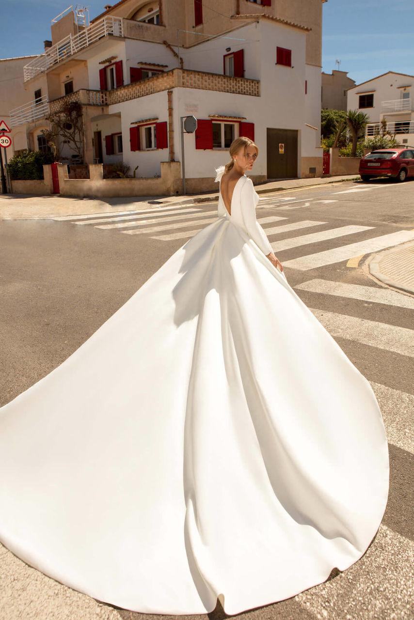 Langes Brautkleid mit voluminöser Schleppe und tiefem Rückenausschnitt – gesehen bei frauimmer-herrewig.de