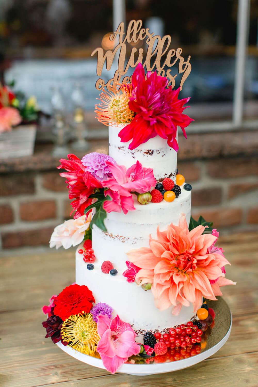 Bunte Hochzeitstorte mit floralen Akzenten – gesehen bei frauimmer-herrewig.de
