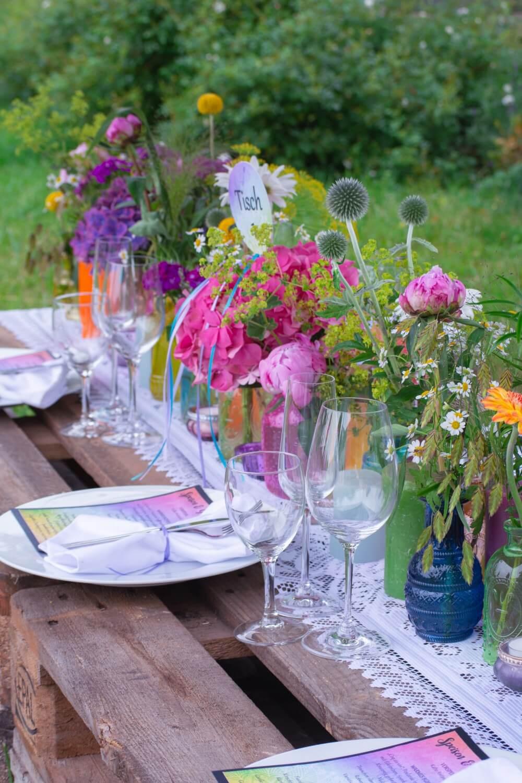 Bunte Tischdeko mit Blumen für Outdoor-Hochzeit – gesehen bei frauimmer-herrewig.de